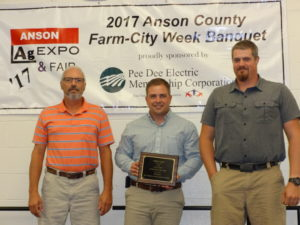 Jake Barbee, Soil & Water Resource Conservationist, presents the Conservation Farm Family Award to Galen and Kyle Barkman of Barkman Farms.