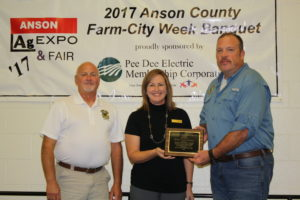 Shelby Emrich, Chamber Director, presents the Outstanding Agribusiness Award to Jeff Poplin and Robert Stovall with Brown Creek Creamery.