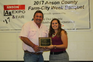 Jessica Morgan, Agricultural Agent, presents the Outstanding Farmer of the Year Award to Todd Moore.